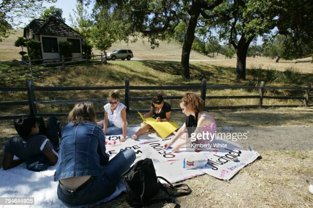 European fans of pop singer Michael Jackson make signs in front of his Neverland Valley Ranch where the entertainer has retreated while waiting the...
