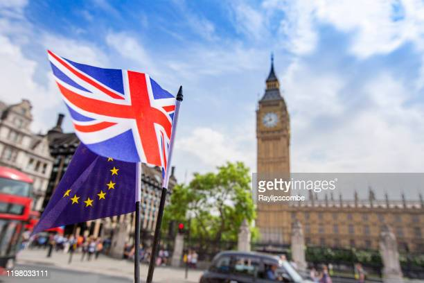 european flag flying alongside the british union jack in front of the houses of parliament, westminster, london. - brexit stock pictures, royalty-free photos & images