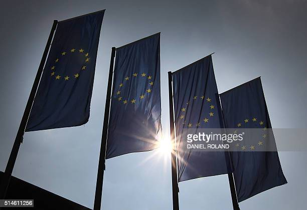 European flags flutter in front of the headquarters of the European Central Bank in Frankfurt am Main western Germany on March 10 2016 The European...