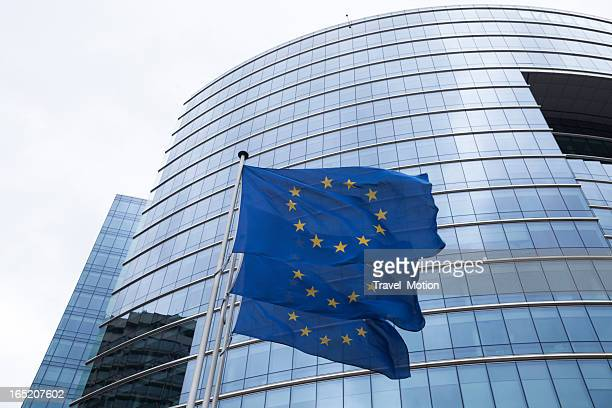 European flags in front of glass office building in Brussels