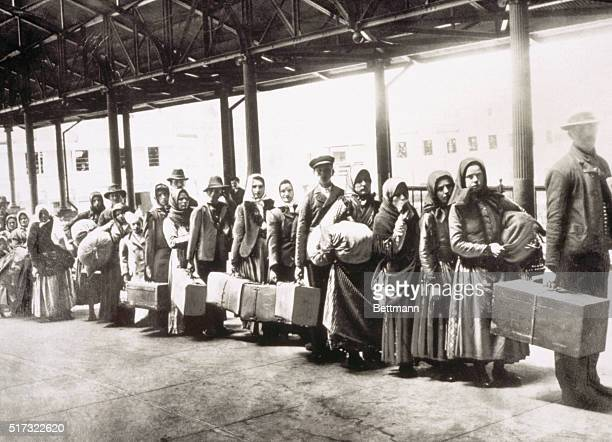 European immigrants who have passed through the entry station at Ellis Island wait for the ferry that will transport them to New York City