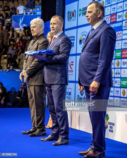 European Judo Union President Sergey Soloveitchik centre briefly holds the EJU flag that he received from the Israel Judo Association President Moshe...