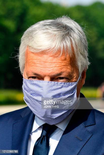 European Justice Commissioner Didier Reynders wears a protective face mask to lessen the spread of novel coronavirus COVID19 as he attends an event...