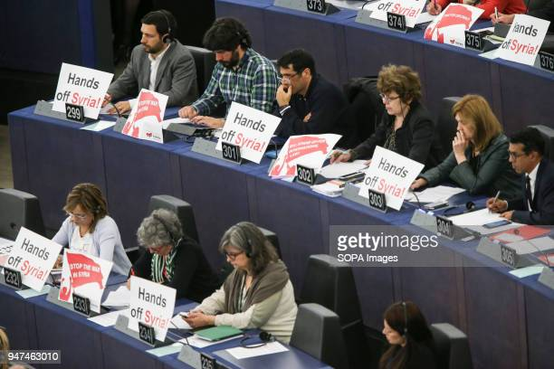 European lawmakers seen holding placards writting on it 'Stop the War in Syria' in protest against airstrikes launched by the United States of...