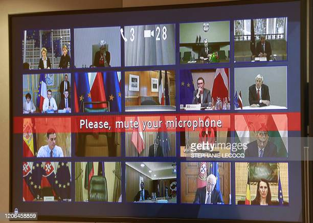 European leaders are seen on a screen as they take part in a conference call with European Council President regarding the novel coronavirus COVID19...