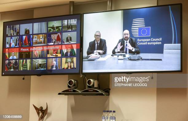European leaders are seen on the screen as they take part in a conference call with European Council President Charles Michel regarding the novel...