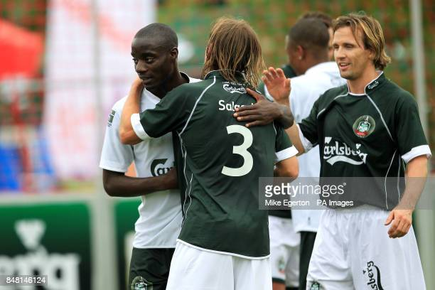 European Legends' Michel Salgado and Boudewijn Zenden embrace with an International FC player at the final whistle