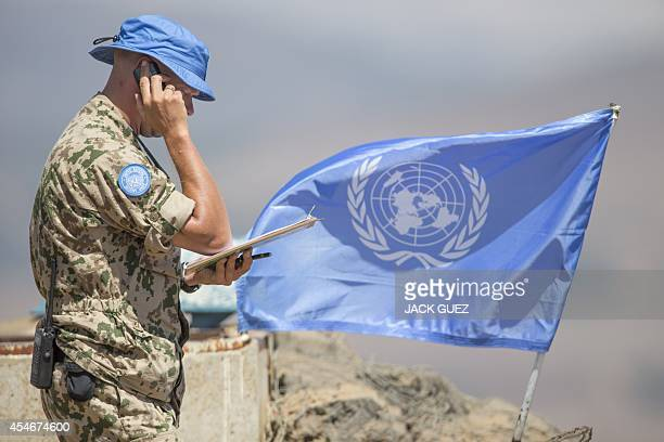 A European member of United Nations Disengagement Observer Force speaks on a phone as he looks at a map at his position in the Israelioccupied Golan...
