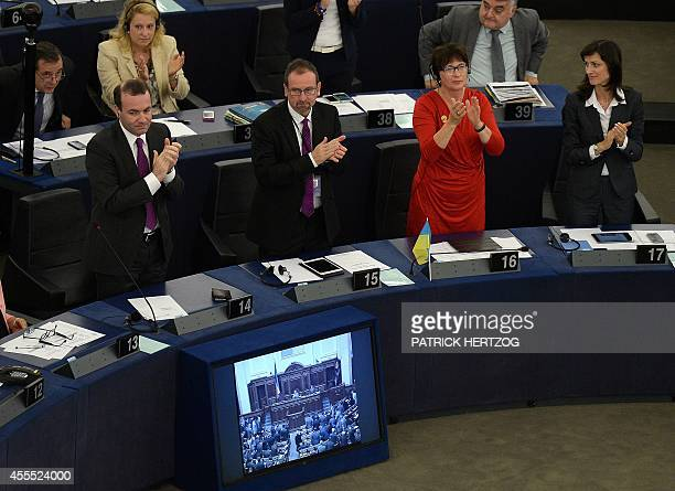 European MP's aupplaud during a videolink with lawmakers in Kiev as legislators voted to ratify a pact at the European Parliament on September 16 in...