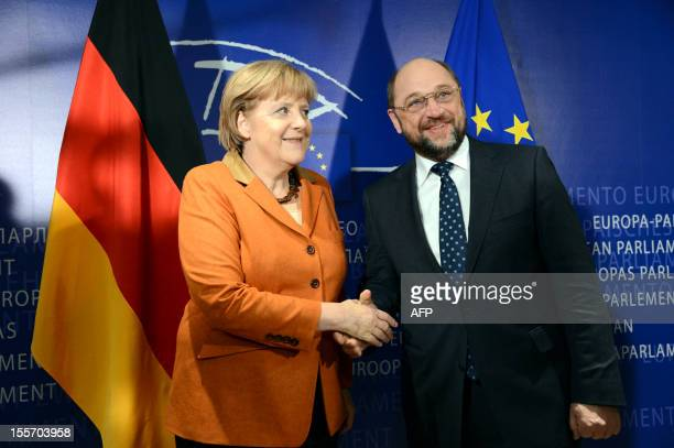 European Parliament President Martin Schulz shakes hands with German Chancellor Angela Merke prior to take part in a meeting at the European...