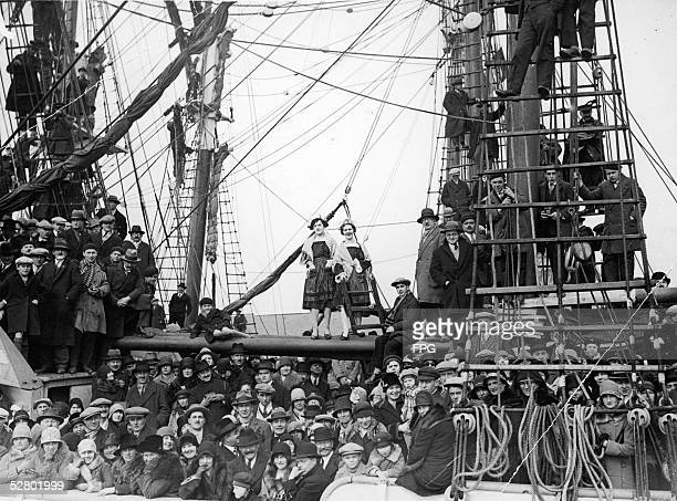 European refugees crowd the deck of what seems to be a sailing vessel as it enters a friendly port late 1930s
