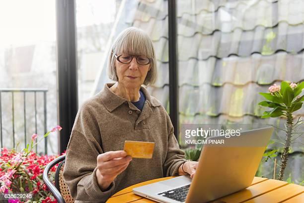 European senior woman home shopping