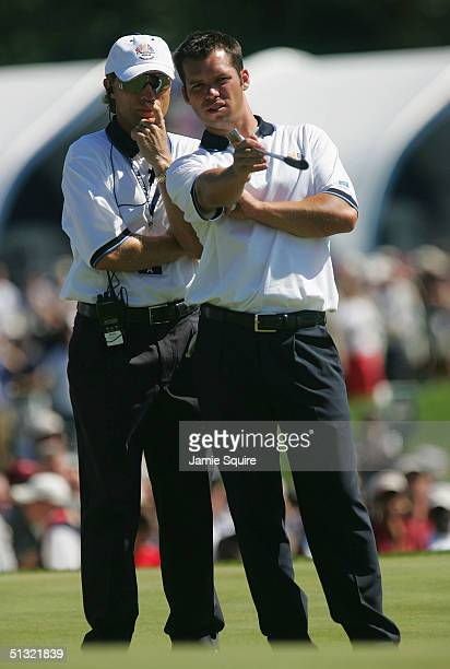European team player Paul Casey iof England chats with European Captain Bernhard Langer during the morning four-ball match with Jim Furyk and Chad...