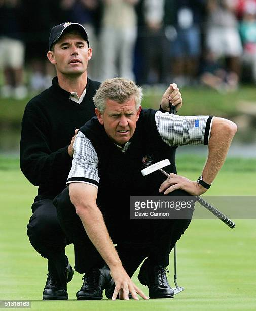 European team players Colin Montgomerie of Scotland and Padraig Harrington of Ireland line up a putt during their four-ball match against Tiger Wood...