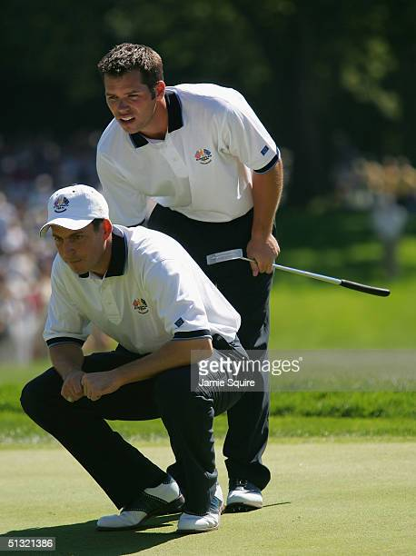 European team players David Howell and Paul Casey of England look over a putt on the 18th green during their morning four-ball match against Jim...