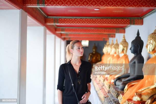 European tourist beautiful woman is visiting at Wat Pho in Bangkok, Thailand.