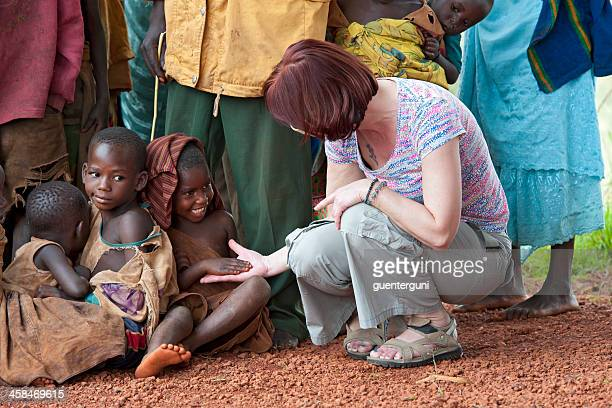 european tourist is playing with african children, burundi - burundi east africa stock pictures, royalty-free photos & images