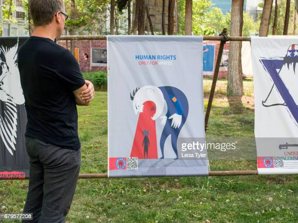 European tourist looks at a poster declaring 'Human rights are only for whites' at the Museum Garden of Anti Arrogance housed in the former American...