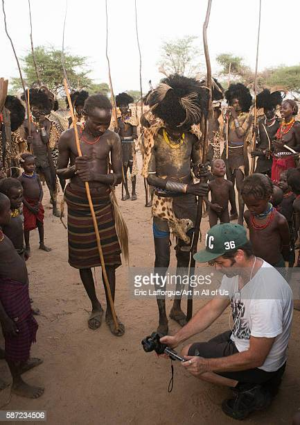 European tourist showing the screen of his camera in dassanech tribe omo valley omorate Ethiopia on March 20 2016 in Omorate Ethiopia