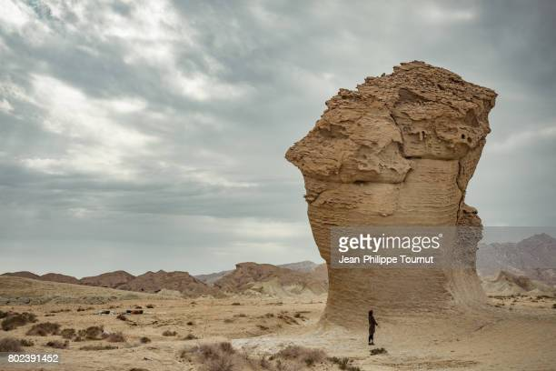 european tourist woman standing by a large rock formation in the desert in southern iran (hormozgan province) - erodiert stock-fotos und bilder