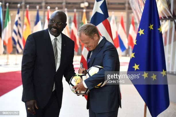European Union Council President Donald Tusk and President of Liberia George Weah sign football balls prior to a meeting at the EU headquarters in...