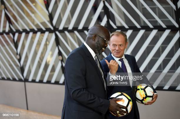 European Union Council President Donald Tusk and President of Liberia George Weah hold football balls prior to a meeting at the EU headquarters in...
