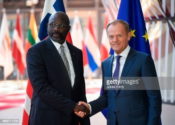 European Union Council President Donald Tusk welcomes President of Liberia George Weah prior to a meeting at the EU headquarters in Brussels on June...