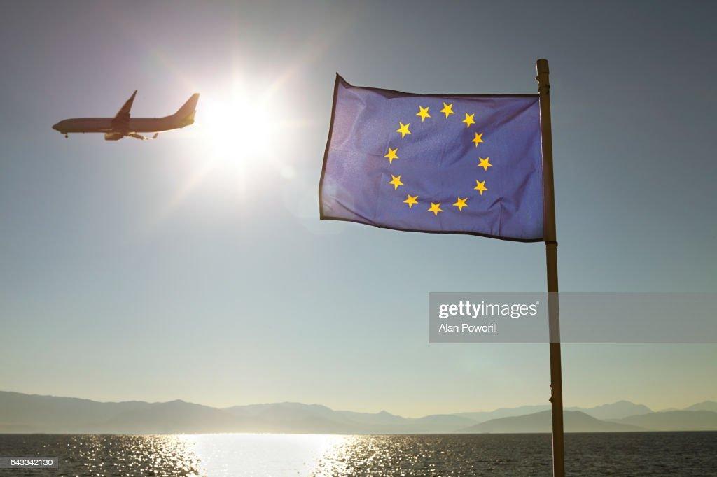 European Union Flag Against Sun & Sea With Plane : Stock Photo