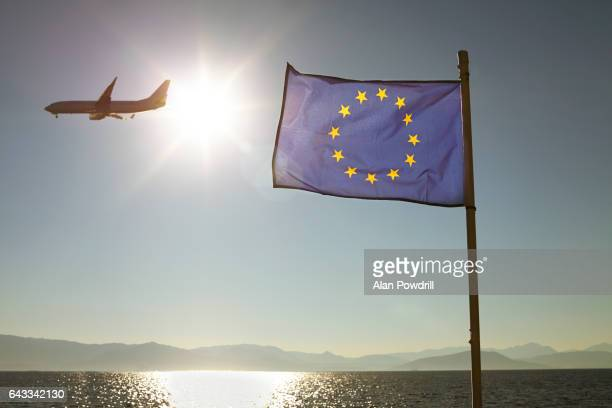 european union flag against sun & sea with plane - brexit stock pictures, royalty-free photos & images