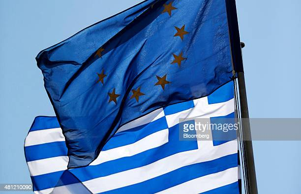 A European Union flag and a Greek national flag fly in central Athens Greece on Saturday July 18 2015 Greek banks will reopen on Monday as Prime...
