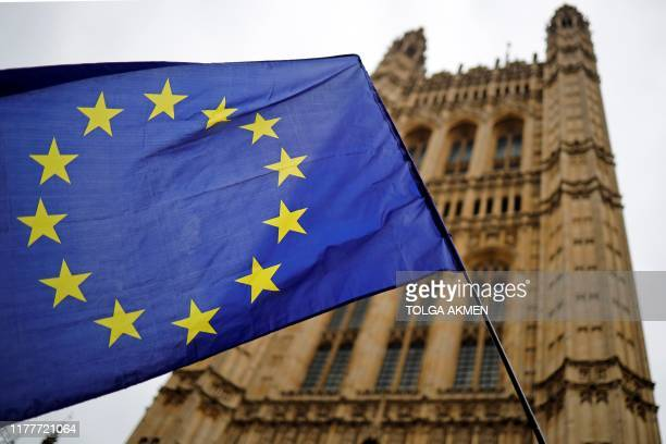 A European Union flag and belonging to an antiBrexit activist flies outside the Houses of Parliament in London on October 23 2019 British Prime...