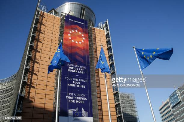 European Union flag fly in front of the European Commission headquarters with a new banner with the lettering reading 'For a union that strives for...