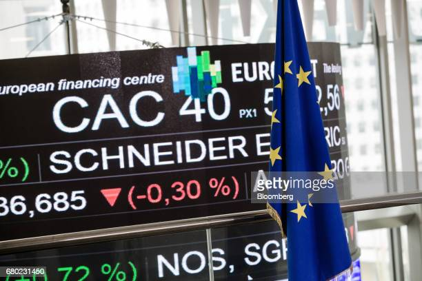 A European Union flag hangs in front of a board displaying company stock price information inside the Paris stock exchange operated by Euronext NV in...