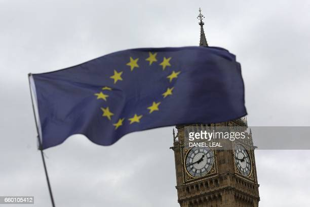 A European Union flag is held by an antiBrexit protester in Parliament Square with Elizabeth Tower in the background in London on March 29 after...