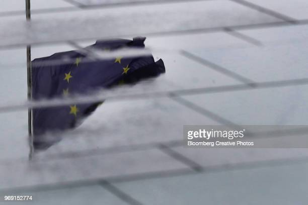 A European Union (EU) flag is reflected in a puddle outside the Chancellery building in Berlin
