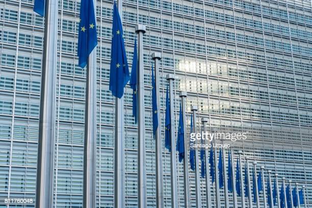 european union flags at berlaymont building of the european commission - legislación fotografías e imágenes de stock