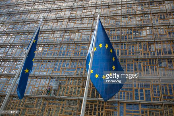 European Union flags fly as window cleaners work on the outside of the Europa Building ahead of a Eurogroup meeting of finance ministers in Brussels...