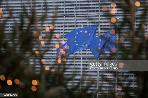 European Union flags fly outside the European Commission building in Brussels, on December 7, 2020.