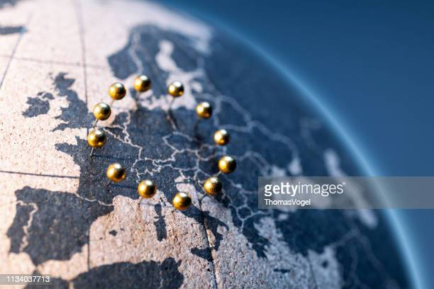 european union - golden pins on cork board globe - international politics stock pictures, royalty-free photos & images