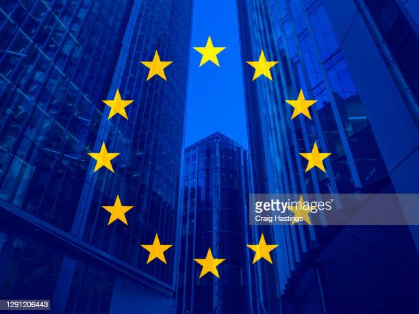 european union politics, business and finance concept piece with the eu flag overlaying skyscrapers and corporate buildings in the background. - european union stock pictures, royalty-free photos & images