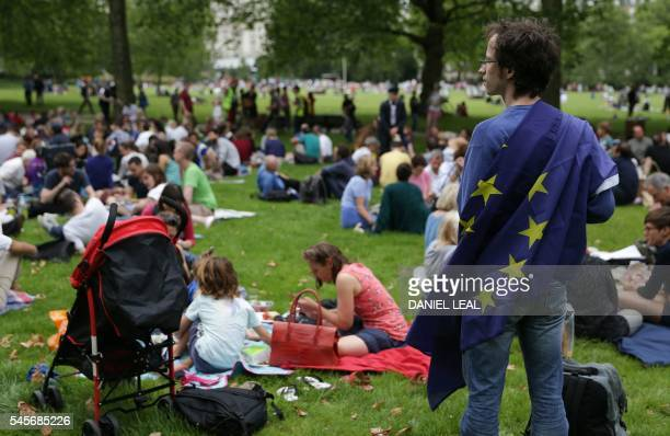 A European Union supporter stands with a European Union flag during a picnic against Brexit organised by the General Assembly in Green Park in London...