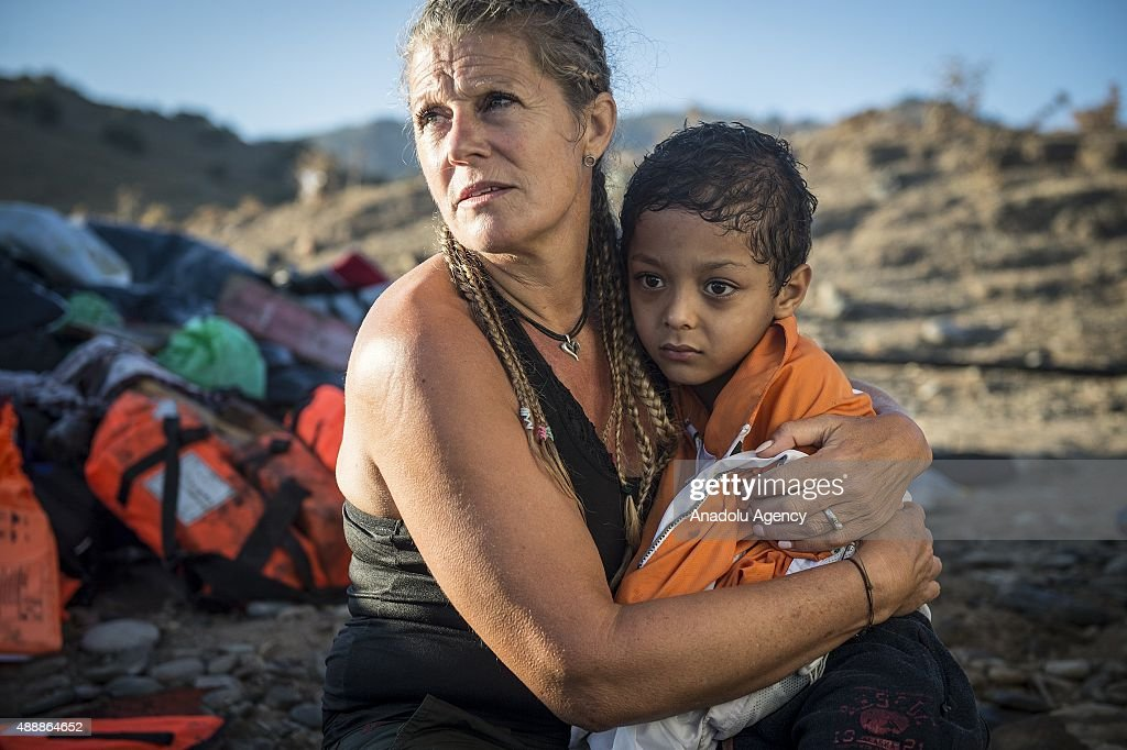 A European volunteer holds a refugee child on her lap after a boat carrying refugees arrived in Lesbos Island, Greece on September 18, 2015. Refugees who begin a journey with a hope to have high living standards away from conflicts, continue using Greece's Lesbos island as a transit point on their way to Europe. Many refugees who get the boats from Turkey's Canakkale and Balikesir, usually land on Eftalou region of Mithymna city.