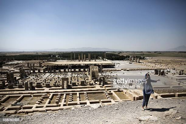European woman gestures over the ruins of the ancient Persian city of Persepolis near Shiraz in southern Iran on September 26, 2014. At the foot of...