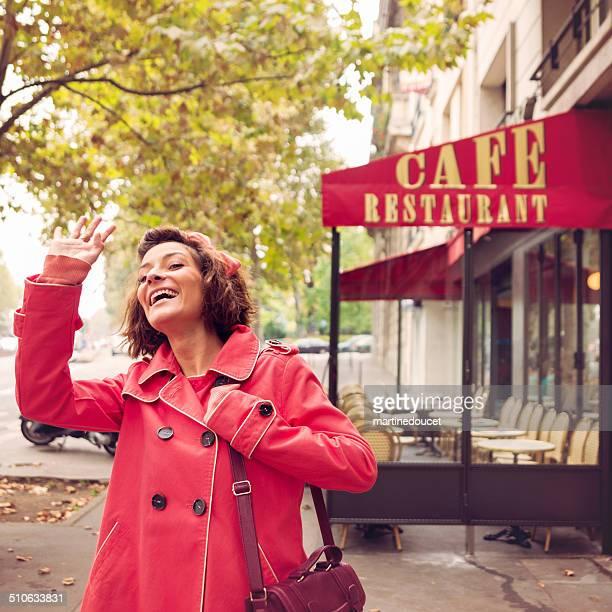 Jeune femme européenne accueillir des amis près du restaurant jours de pluie.