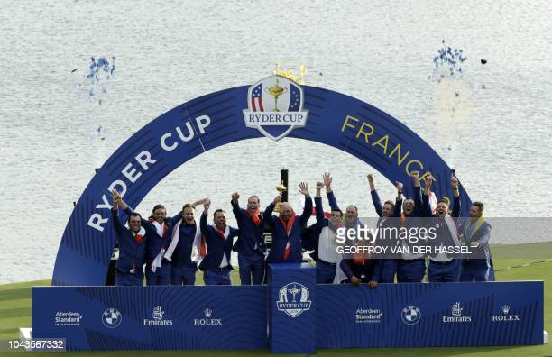Europe's Danish captain Thomas Bjorn raises the trophy flanked by his team as they celebrate winning the 42nd Ryder Cup at Le Golf National Course at...