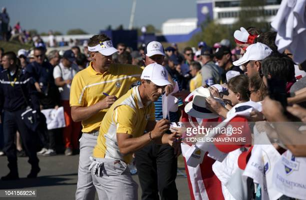 Europe's Danish golfer Thorbjorn Olesen and Europe's English golfer Ian Poulter sign autographs for spectators during a practice session ahead of the...