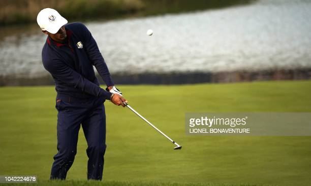 Europe's Danish golfer Thorbjorn Olesen plays a chip shot during his fourball match on the first day of the 42nd Ryder Cup at Le Golf National Course...