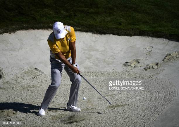 Europe's Danish golfer Thorbjorn Olesen plays a shot out of a bunker during a practice session ahead of the 42nd Ryder Cup at Le Golf National Course...