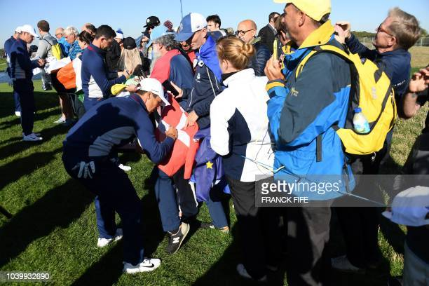 Europe's Danish golfer Thorbjorn Olesen signs autographs for spectators during a practice session ahead of the 42nd Ryder Cup at Le Golf National...