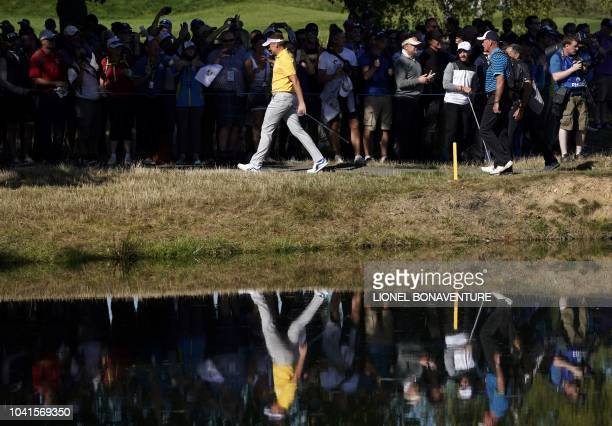 Europe's English golfer Ian Poulter is reflected in water as he walks during a practice session ahead of the 42nd Ryder Cup at Le Golf National...